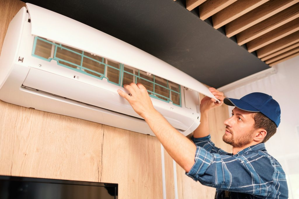 Young technician opening lid of air conditioner to check what is wrong with it