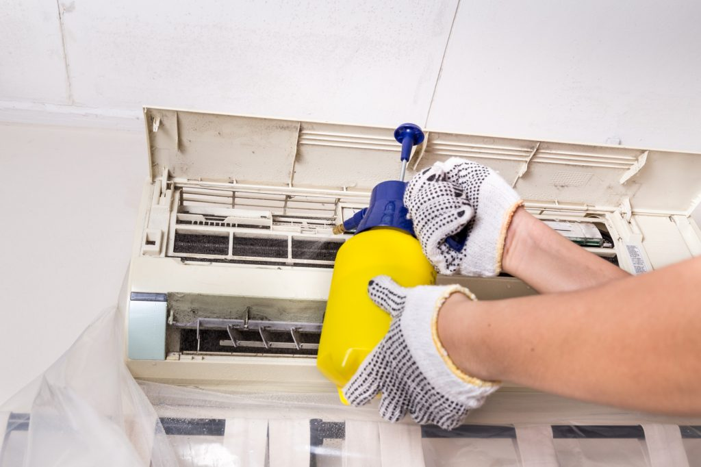 Technician spraying chemical water onto air conditioner grid to