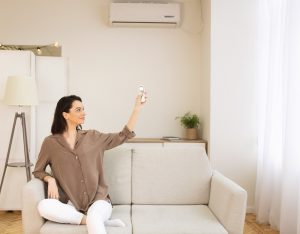 Young woman switching on air conditioning sitting on sofa