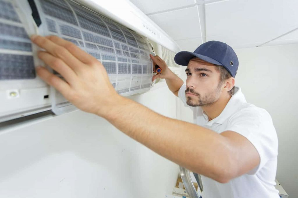 portrait of mid adult male technician repairing air conditioner